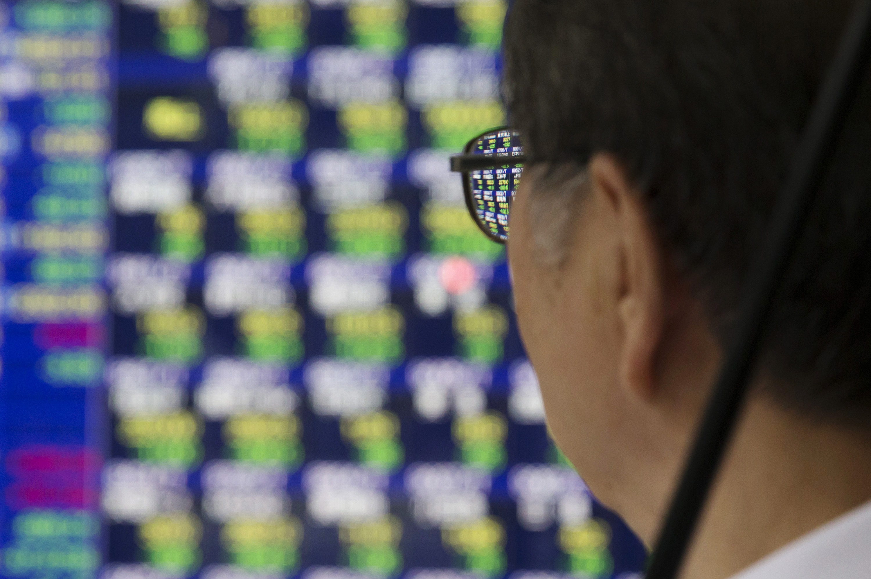 A pedestrian looks at an electronic stock board displaying financial data outside a securities firm in Tokyo, Japan.
