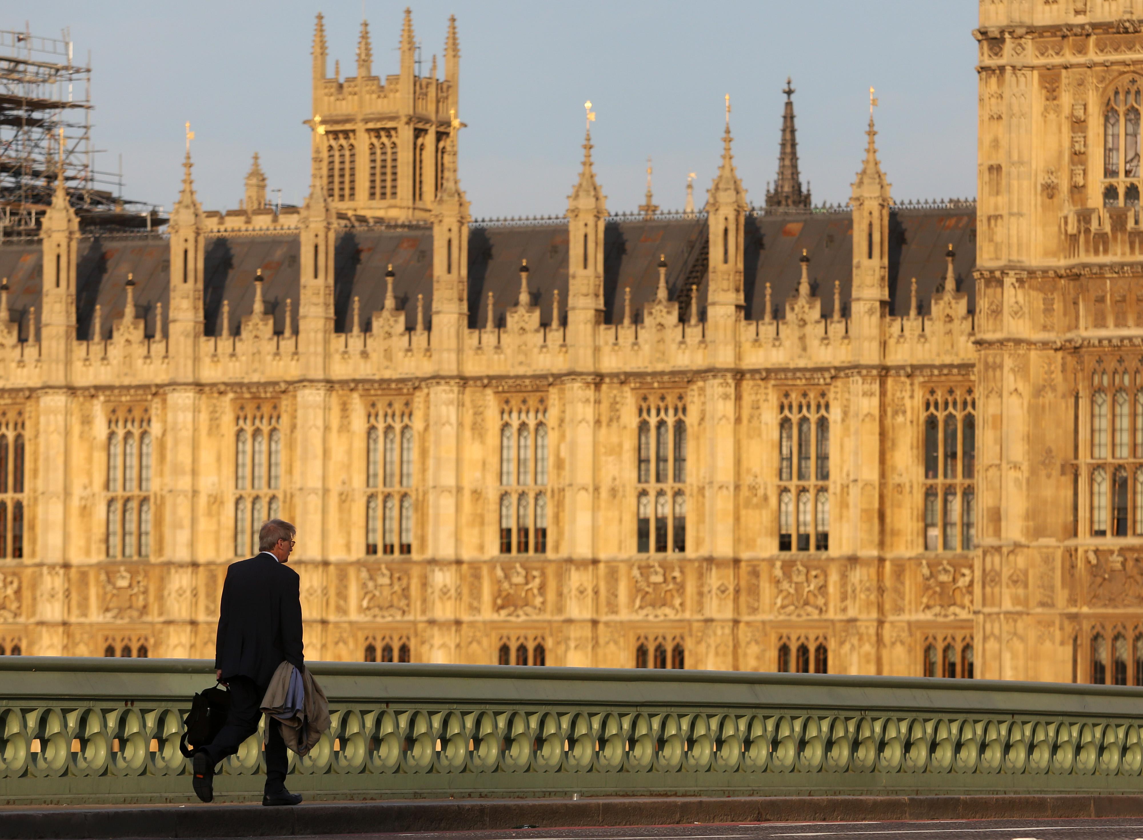 A pedestrian walks across Westminster bridge towards the Houses of Parliament in London, U.K.