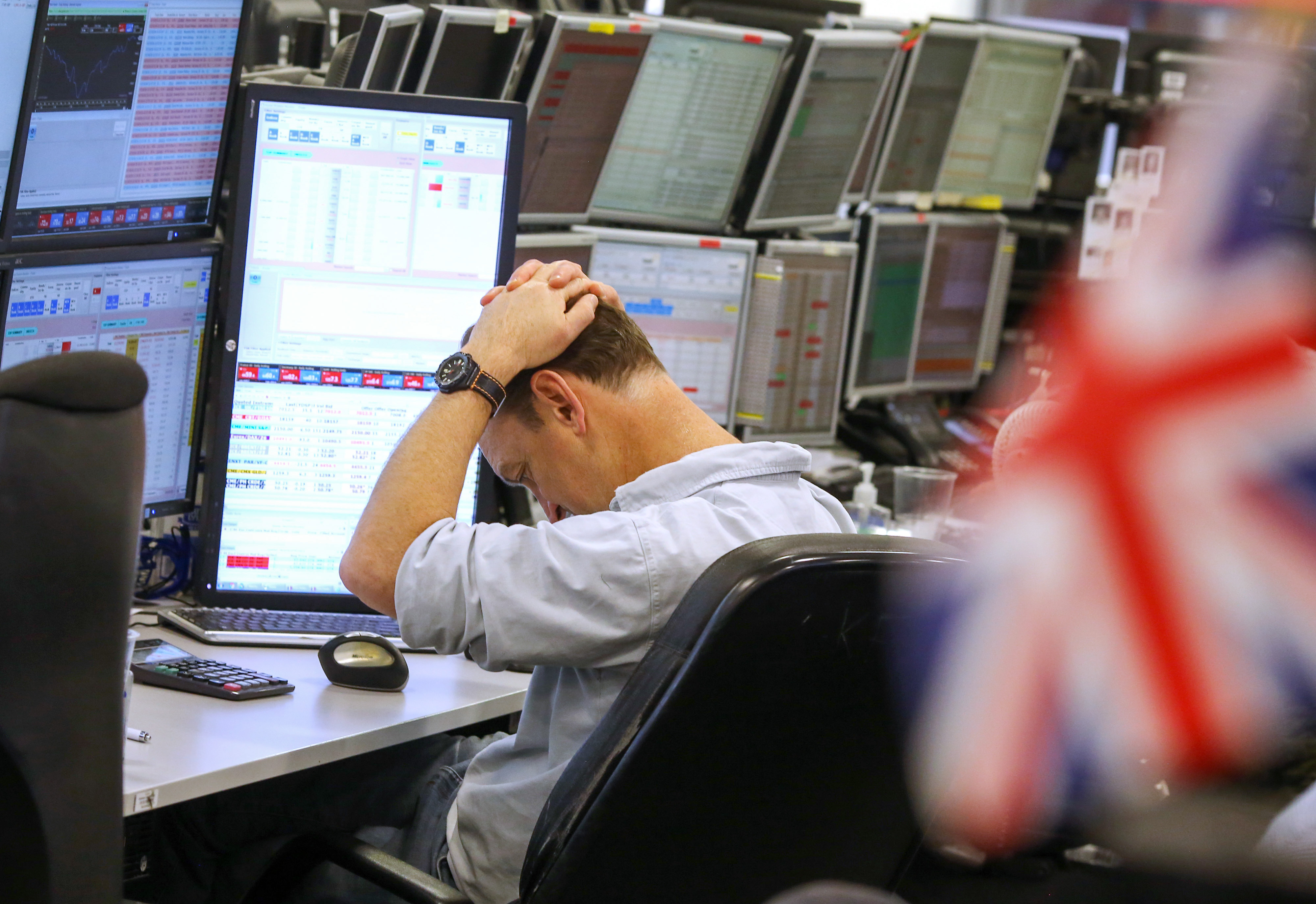 A trader pauses while monitoring financial data on computer screens at ETX Capital, a broker of contracts-for-difference, in London, U.K