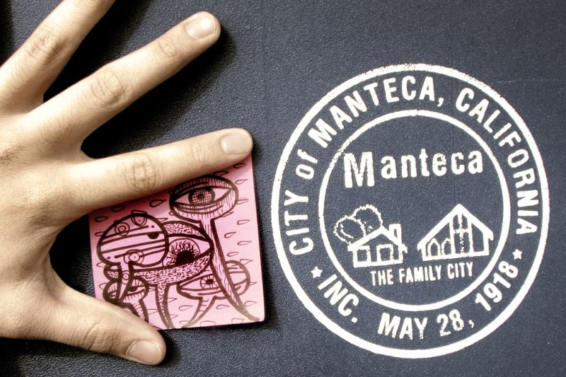 Hand with Post-It note next to Manteca, CA seal.