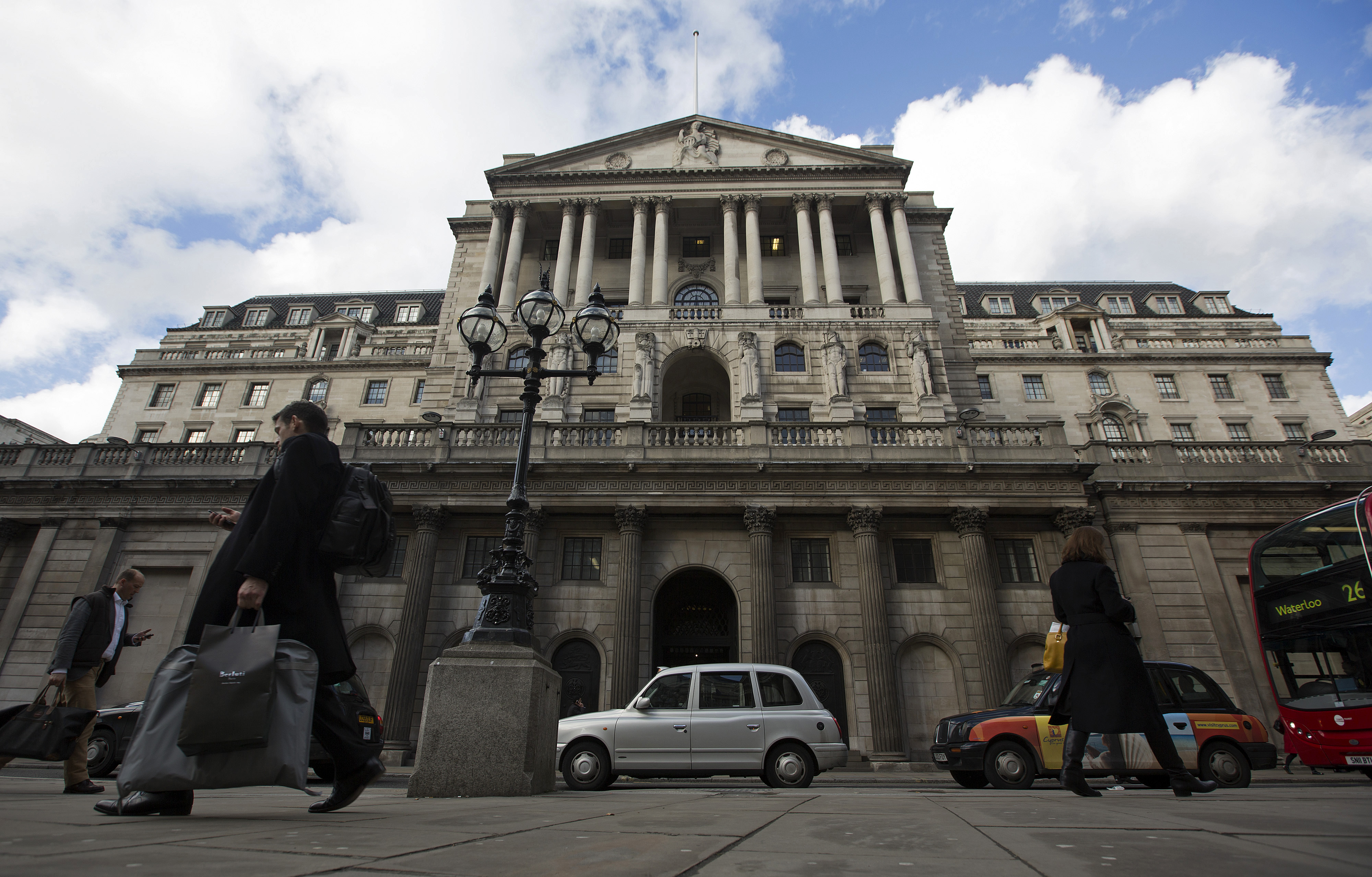 Pedestrians and London taxi cabs pass the Bank of England in London, U.K.