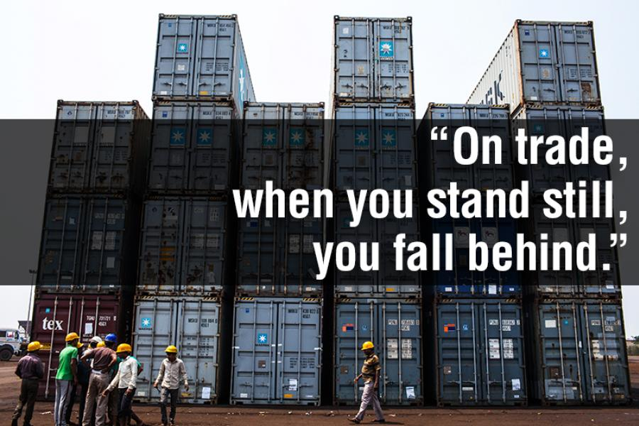 A group of workers stand beside containers stacked at the Haldia Dock Complex.