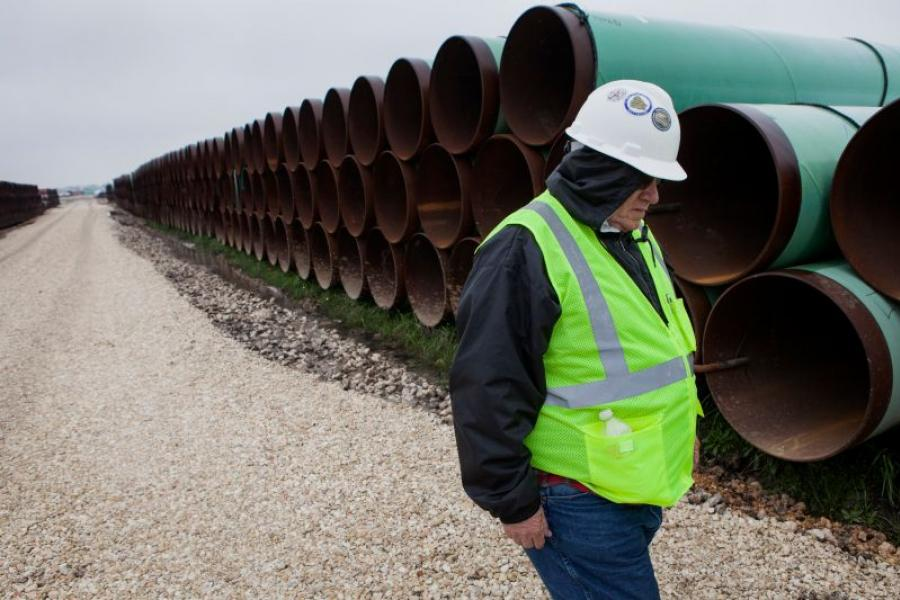 A worker walks past pipe ready to be used to construct the Keystone XL pipeline. Photographer: Photographer: Scott Dalton/Bloomberg.