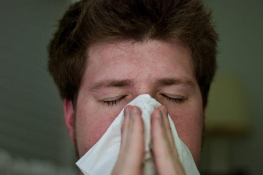 Man sneezes into a tissue.