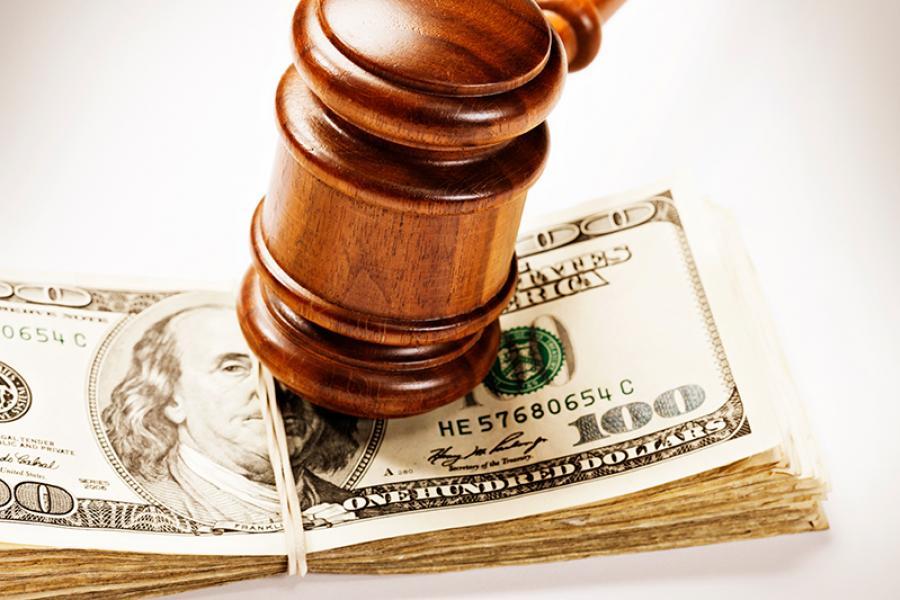Judge's gavel on top of $100 bills.