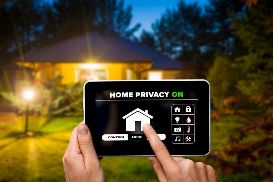 """Home privacy"" displayed on app on a tablet computer in front of a house."