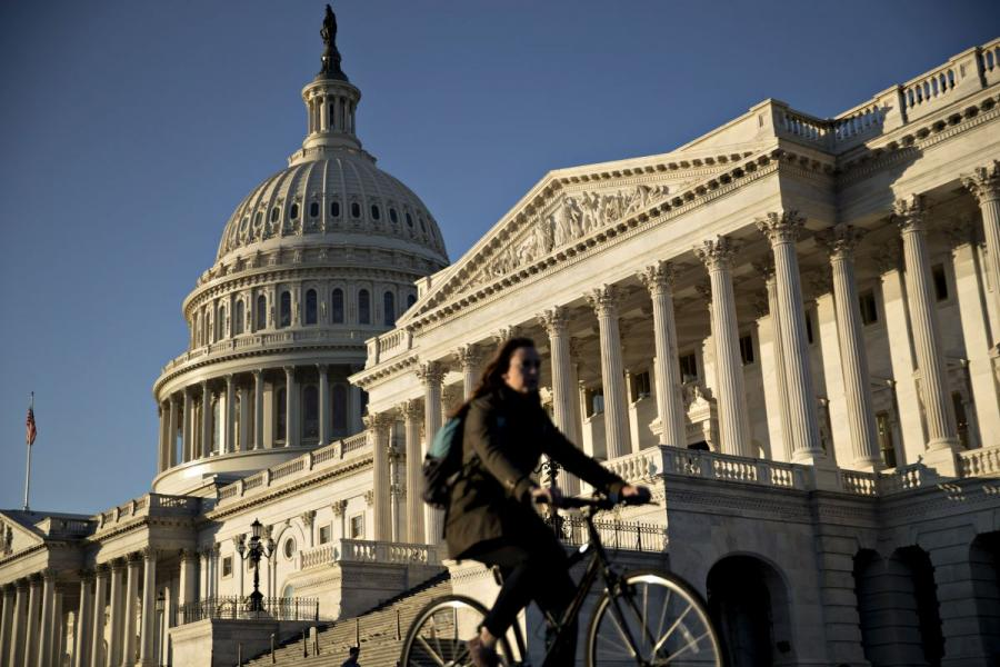 A bicyclist rides past the U.S. Capitol in Washington, D.C.