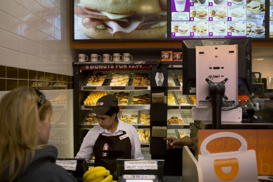 An employee assists a customer at a Dunkin Donuts franchise in New York.