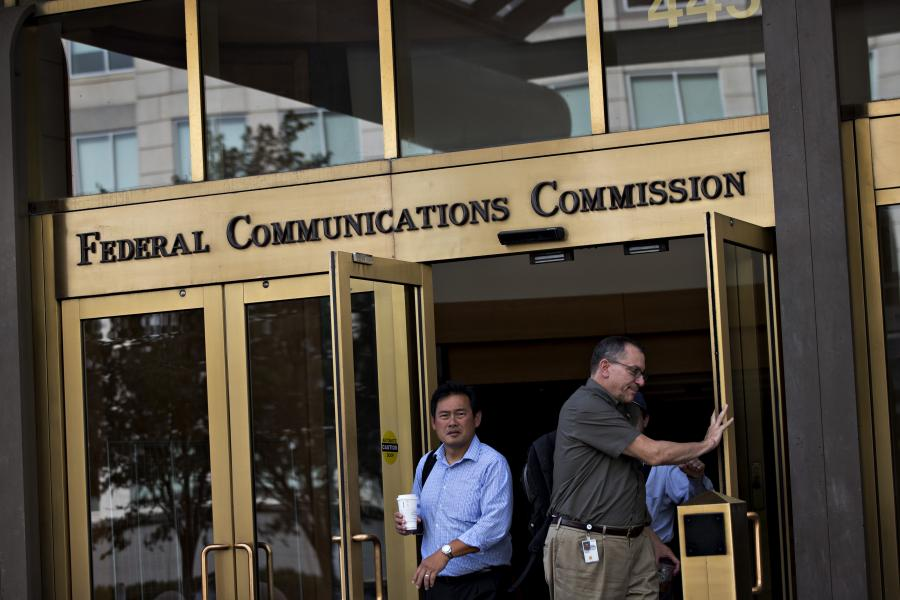 People walking out of the Federal Communications Commission headquarters in Washington, D.C.