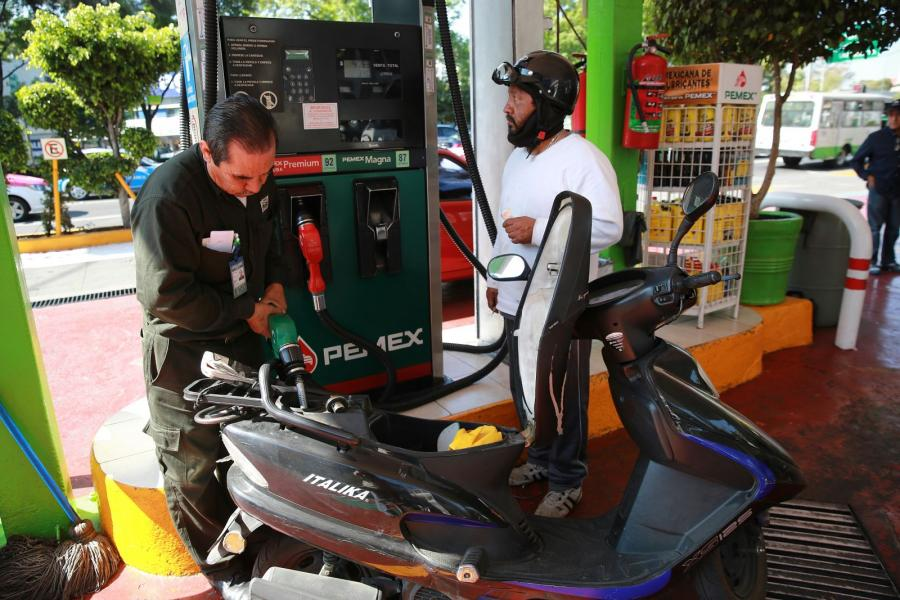 A PEMEX employee fuels a scooter at a company gas station in Mexico City, Mexico.