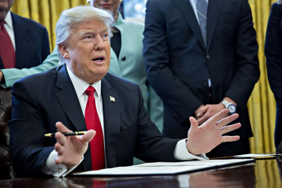 With business leader surrounding him, President Donald Trump signs an executive order taming federal regulators.
