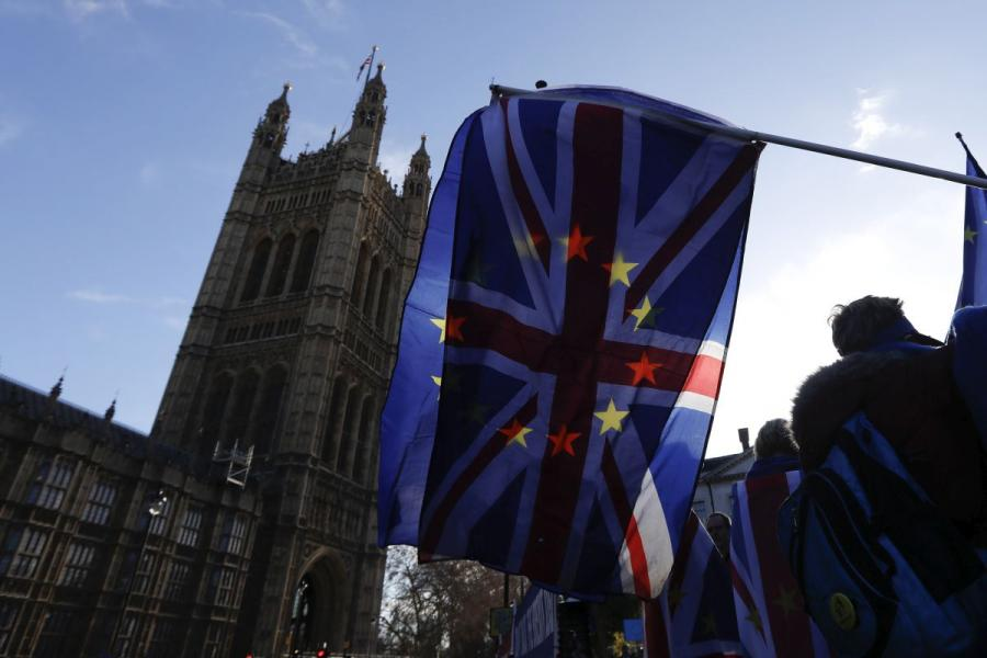 The British Union Jack flag flies beside a European Union flag outside the Houses of Parliament in London.