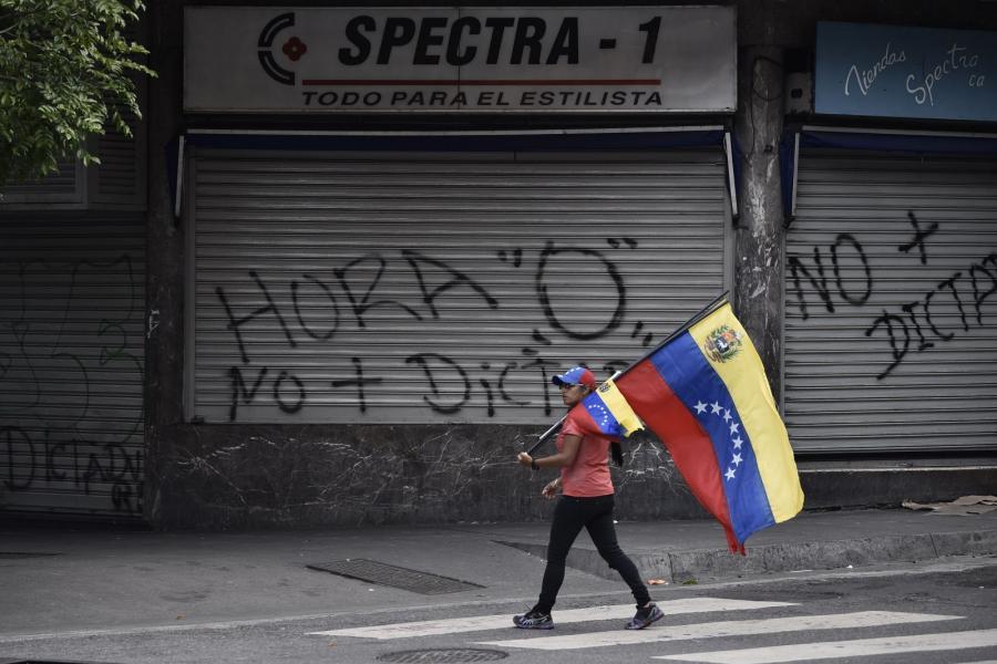 A pedestrian carries a Venezuelan flag during a national strike in Caracas, Venezuela.