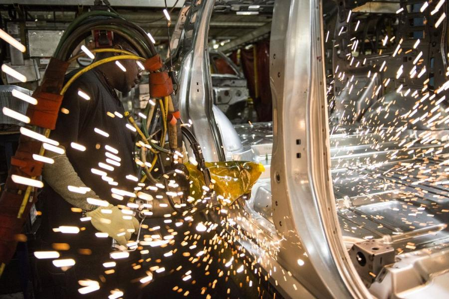 An employee welds together a frame for a sports utility vehicle at the General Motors assembly plant in Arlington, TX.
