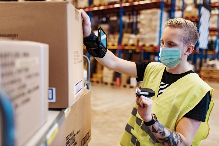 Young Man in warehouse uniform stacks boxes and organizes boxes