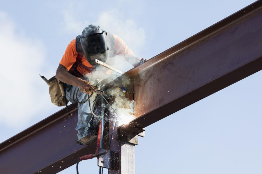 A male steel worker working high up on a girder. He is sitting on the girder, wearing a safety harness, welding to secure the girder to a column.