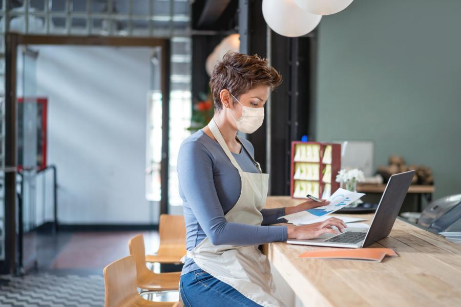Business owner wearing a facemask while bookkeeping at a restaurant using a laptop during the COVID-19 pandemic