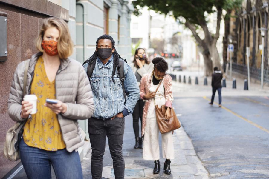 Diverse group of people wearing face masks and standing in a long line outside of a building
