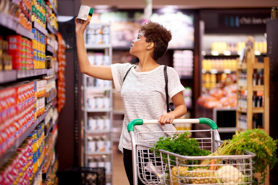 Young woman check prices on cans in a grocery store aisle.