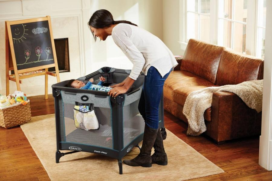 Mother playing with a baby in a Graco Bay Products play pen.