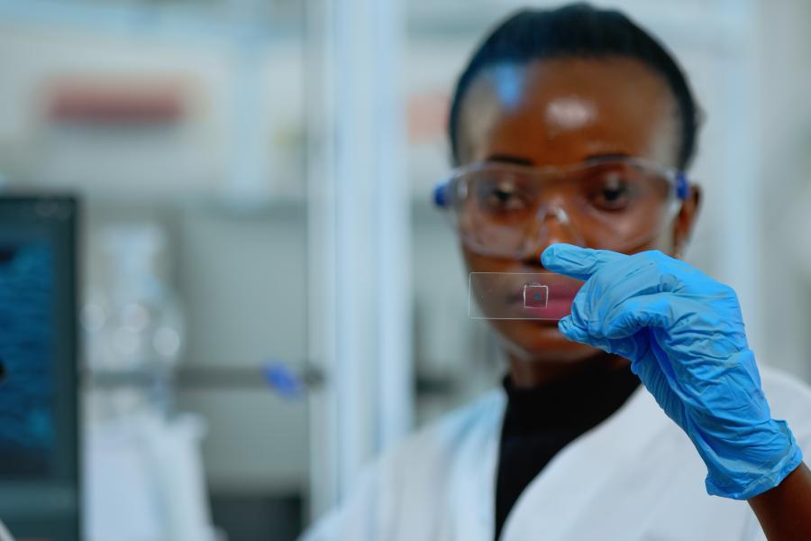 Black, female scientist examines slide.