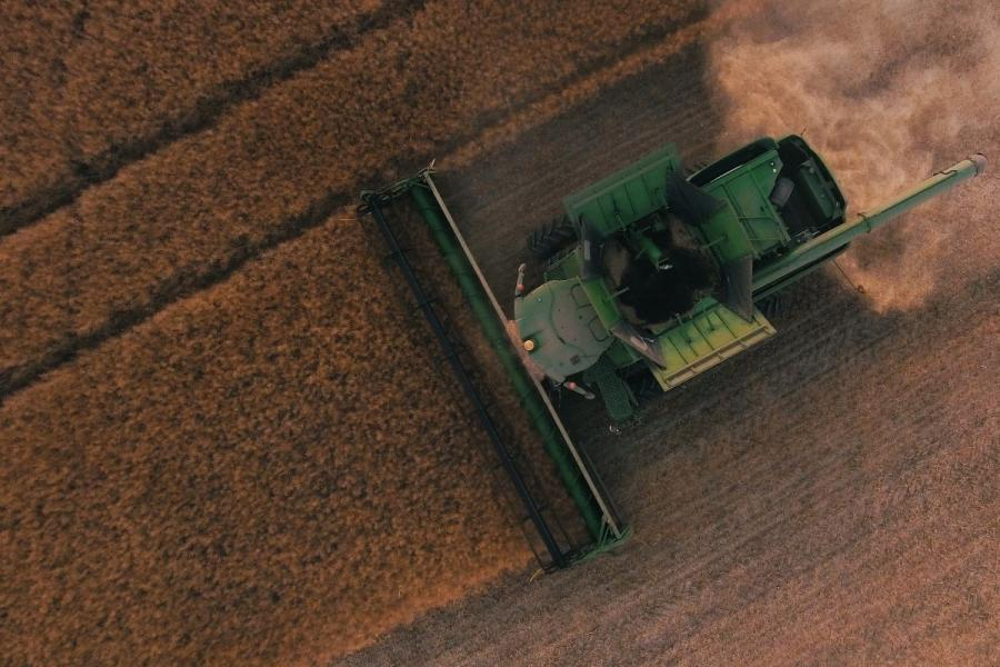 Green combine harvesting a field.