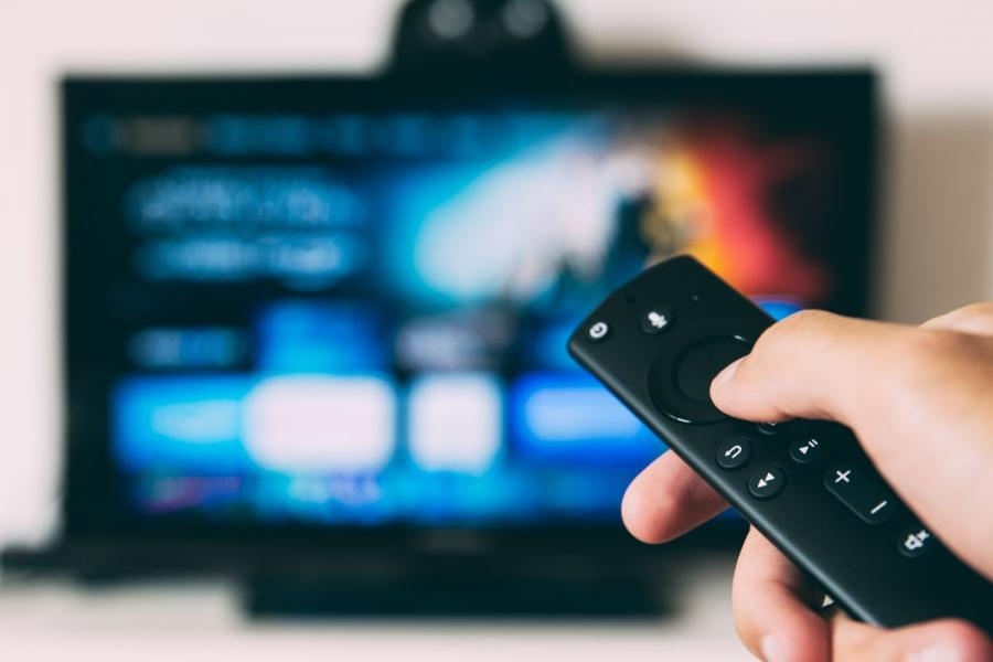 A hand holding a remote control for a video streaming device.
