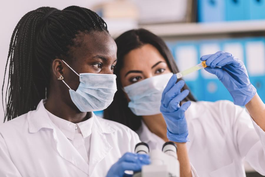 Two women of color work performing scientific research in a lab