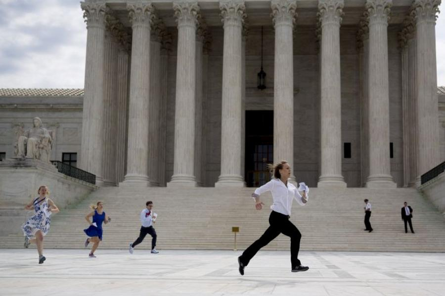 Interns outside the Supreme Court run the Obamacare tax subsidies opinion to colleagues.