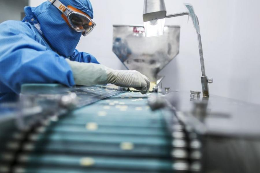 A worker inspects tablets moving along the production line in a pharmaceutical plant in India.