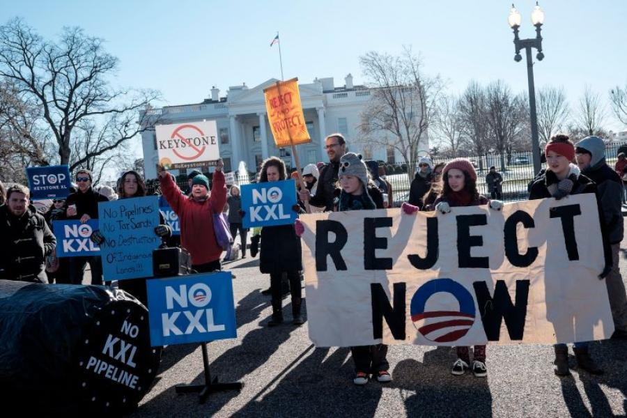 Demonstrators hold signs during a rally against the Keystone XL pipeline outside of the White House.