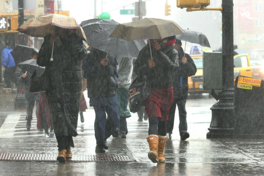 Pedestrians shield themselves with umbrellas as they walk down a rain soaked street in the Brooklyn.