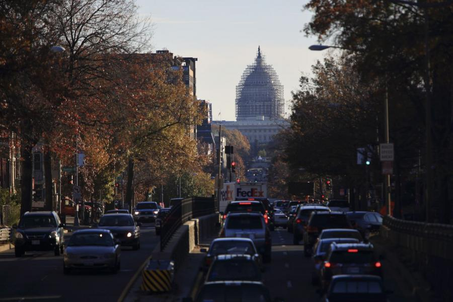 Vehicles move in front of the U.S. Capitol building.
