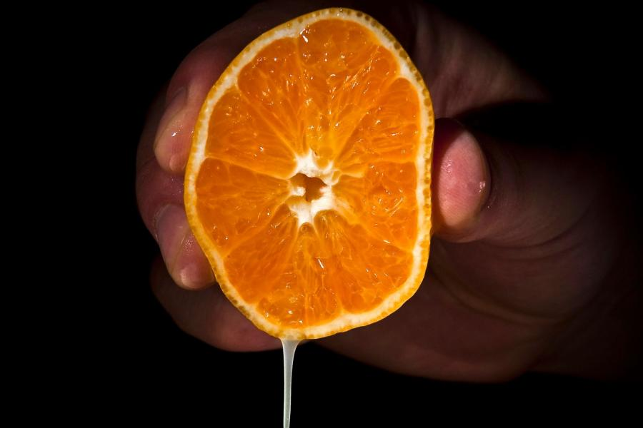 A hand squeezing an orange.