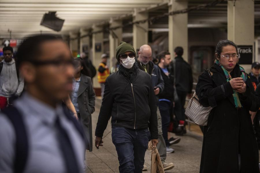 A commuter wears a mask while walking through a subway station in New York City.