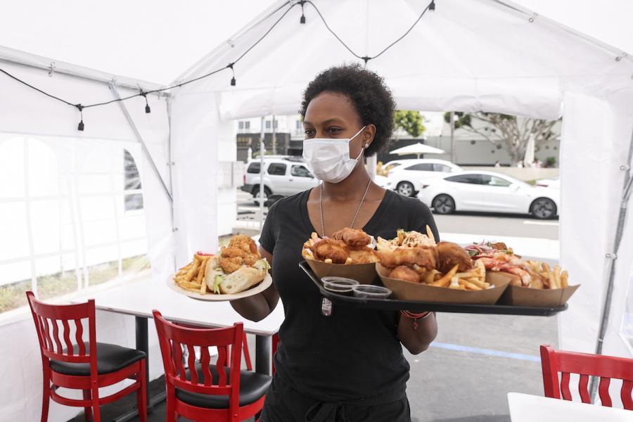 Food server in a mask working in a tent.