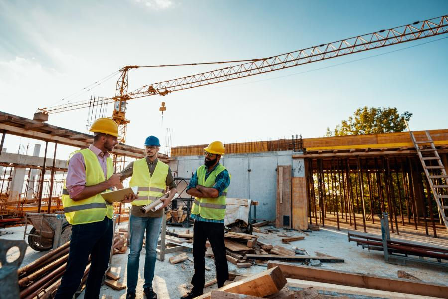 Three male construction workers discuss construction plans on a commercial construction site.