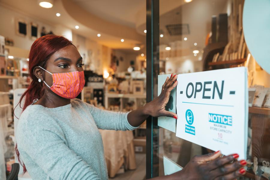 Small business owner applying an -OPEN- sign to the entrace door with the safety measures to respect during Covid-19 pandemic.
