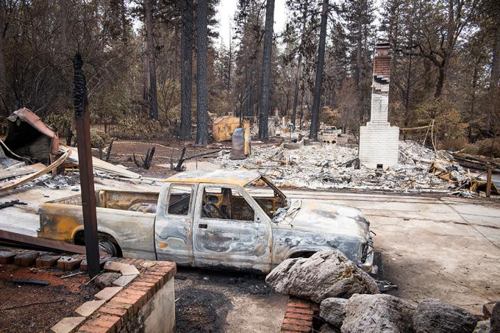 A burned-out vehicle is seen near destroyed homes in Paradise, California.