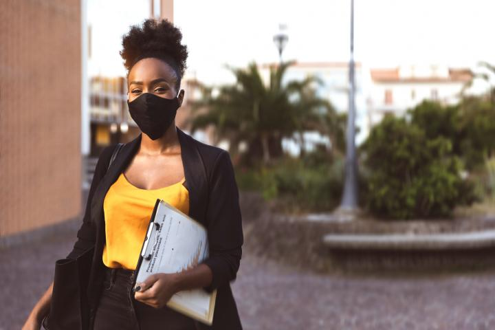 Black woman in a suit walks with business paperwork outside