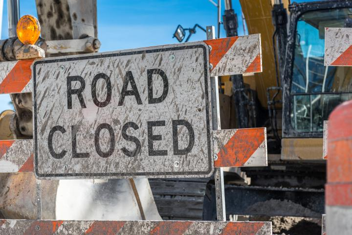 """""""Road closed"""" sign in front of road construction."""