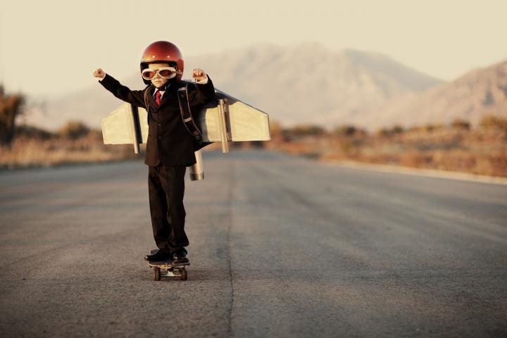 Boy standing on highway, wearing a helmet and airplane wings.