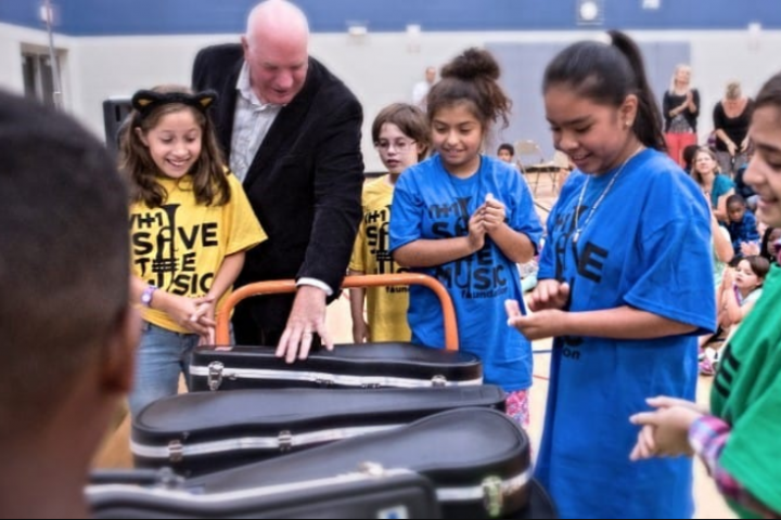 Musicnotes Chairman Tim Reiland helps students unpack new instruments