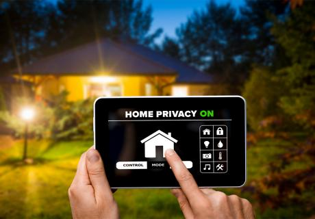 """""""Home privacy"""" displayed on app on a tablet computer in front of a house."""