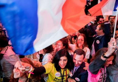 French voters wave flags while waiting for French presidential election results in Paris.