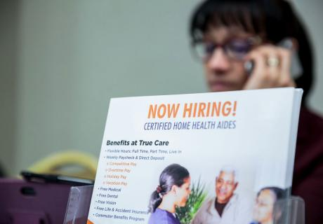 """A """"Now Hiring"""" brochure for home health aides is displayed at a career fair in New York, NY."""