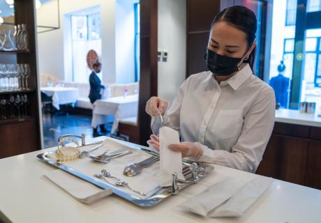 A worker wearing a protective mask places silverware into bags at Jungsik restaurant in New York City.