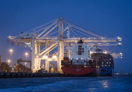A container ship sits docked a the Port of Oakland in Oakland, CA.