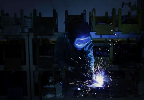 A factory worker welds forklift components together on an assembly line in Indiana.