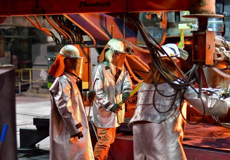 Workers wear protective gear while operating machinery inside a steel plant in Hamilton, Ontario, Canada.